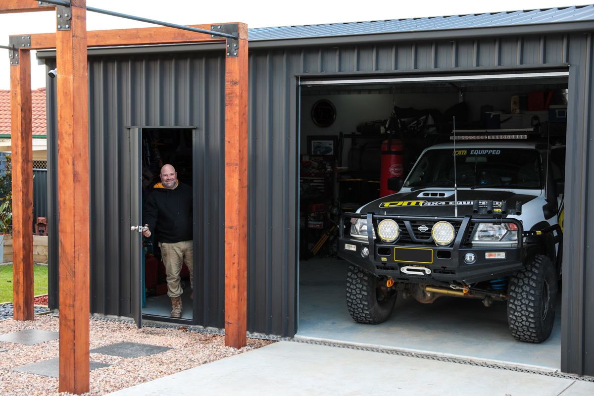 Man holding open the personal access door on his COLORBOND steel matt garage with a four wheel drive parked inside