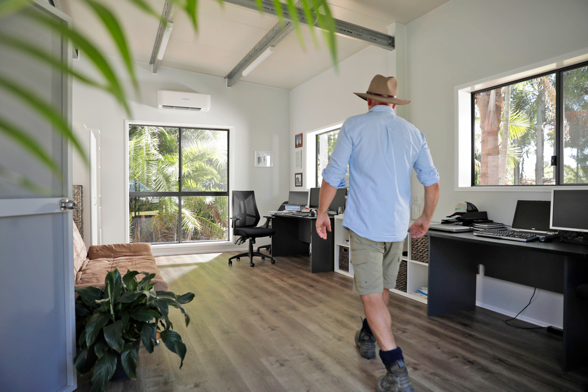 Man walking through a shed home office with plants and computers